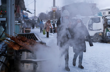 Young women pass by a street food vendor in Blagoveshchensk