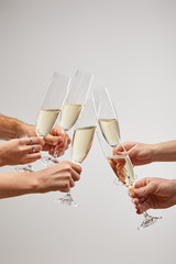 cropped view of men and women toasting champagne glasses with sparkling wine isolated on grey