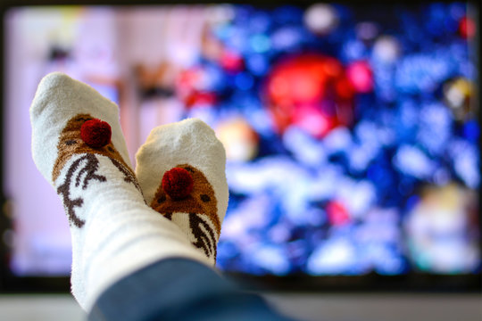 Cozy warm winter christmas socks with a reindeer. Person watching a christmas movie on the television.