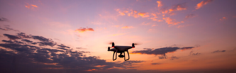 drone quadcopter with digital camera flying at sunset.Dark Flying drone and cloud sunrise sky.