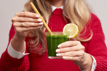 Woman holding fresh spinach green smoothie with bamboo straw