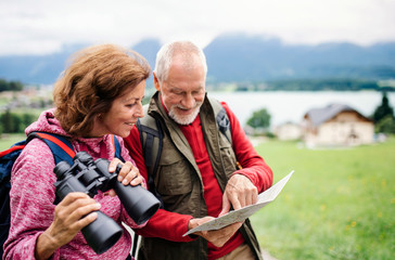 Senior pensioner couple with hiking in nature, using binoculars and map.