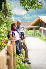 A senior pensioner couple with binoculars hiking, resting. Copy space.
