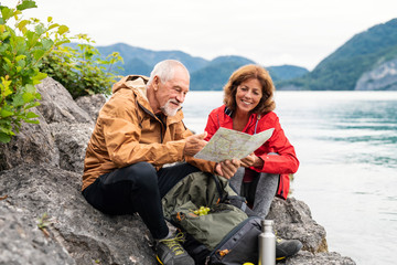 A senior pensioner couple hiking by lake in nature, using map. Fotobehang