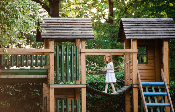 Small girl outdoors on wooden playground in garden in summer, playing.