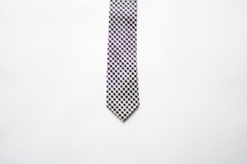 Overhead shot of a purple and white tie on a white surface