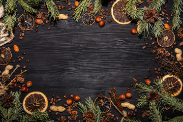 New Year black background with oranges dried, nuts, bumps and spruce
