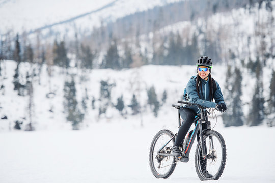 Female mountain biker with bicycle standing outdoors in winter nature.