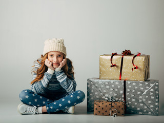 A teenager in a knitted hat and sweater bought Christmas gifts for parents at a low price. The girl is waiting when she can present surprises to her friends for the new year. Holiday discounts
