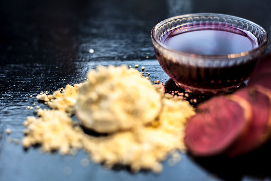 Face mask for a natural glow for all skin types on the black wooden surface consisting of some beetroot juice, yogurt, lime juice, and gram flour. Shot of face mask with entire ingredients.Horizontal
