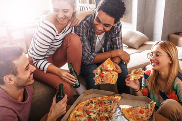 Group of friends making fun at the home party.They sitting in living room and eating pizza.