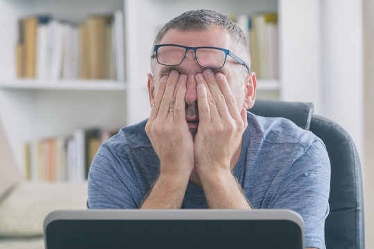 Tired freelancer man rubbing his eye