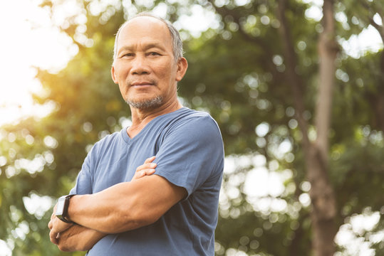 Asian Senior man in blue shirt smiling with arms crossed before exercising.