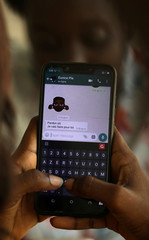 A woman uses Zouzoukwa emojis while chatting on mobile phone in Abidjan