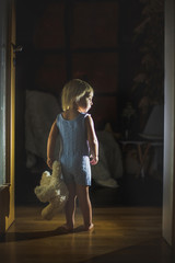 Toddler boy, hodling teddy bear, standing in hallway next to the door to bedroom, fairy tale picture