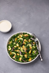 Kale cabbage salad with baked potatoes, cucumber, red onions and mustard yogurt sauce on gray texture background, top view, free space