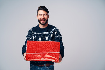 Happy young man giving Christmas present. Isolated on grey background