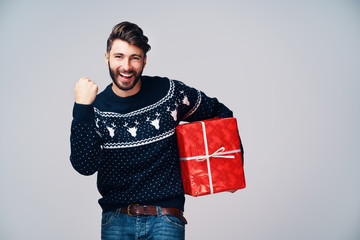 Satisfied young man holding a Christmas present isolated on gray background