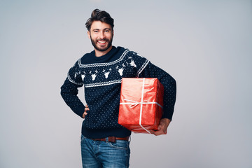 Handsome young man holding Christmas gift smiling. Isolated on grey background
