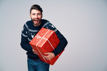 Excited young man screaming while holding Christmas gift. Isolated on grey background