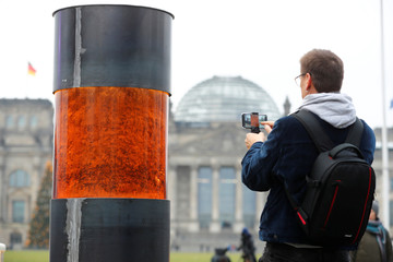 A man takes a picture of a temporary memorial, a column dedicated to the victims of the Holocaust, set up by activists of the 'Zentrum fuer politische Schoenheit' (Center for Political Beauty) in Berlin
