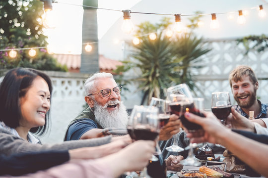 Happy family dining and toasting red wine glasses outdoor - People with different ages and ethnicity having fun in barbecue dinner party - Parenthood youth and elderly weekend activities concept