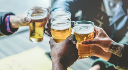 Group of multiracial friends enjoying a beer glasses in brewery english pub - Young people cheering at bar restaurant - Friendship and party concept - Focus on bottom black hand