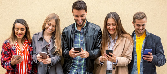 A group of people standing with their smartphones in hand and enjoying online stuff- Friends using celphones and shareing moments- Technology concept