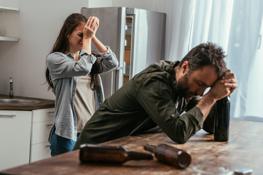 Selective focus of crying woman with alcohol addicted husband on kitchen