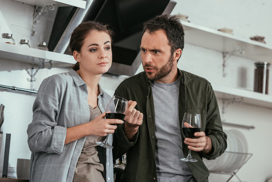 Alcohol addicted couple with wine glasses quarreling on kitchen