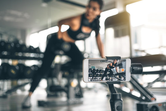 Woman using a phone for vlogging or selfie photo. Asian woman doing workout with dumbbell