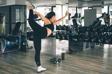 Woman stretching her muscles in yoga posture after workout at the gym