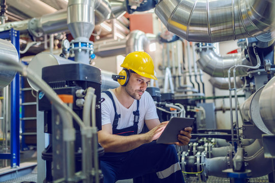 Serious caucasian handsome worker in overall, with hardhat and antiphons crouching and using tablet. Factory interior.