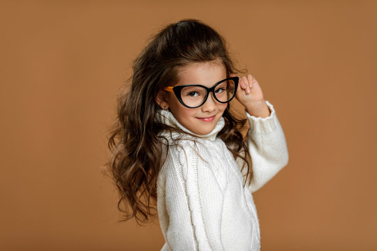 Cute curly little child girl wearing glasses and looking to camera in studio