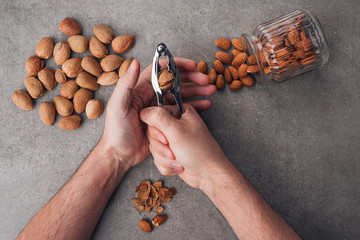 A man pricks almonds. Whole and peeled almonds on a stone surface. Gray background. Top view.