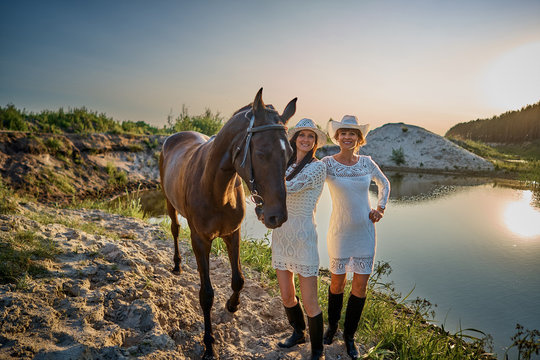 two girls in white dresses on a summer evening with a horse at sunset