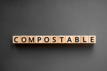 Compostable - word from wooden blocks with letters, biodegradable  compostable concept, top view gray background