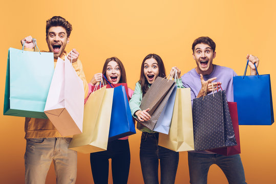 excited young friends shouting and holding shopping bags together, isolated on yellow