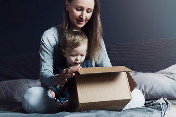 Woman and child sitting on home bed and unwrapping delivered package. Online order of high quality goods at affordable prices: toys, clothing, food. Safe shipment worldwide, money refund guarantee.
