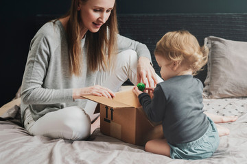 Woman and little child playing with big cardboard box. Mother putting things into package. Female purchasing products for famliy online and receiving them quickly at home address. Easy online payment