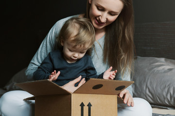 Happy family unwrapping big cardboard box delivered to their house. Online shopping and delivery from international retailers. High-quality goods at big discounts and on special offers through coupons