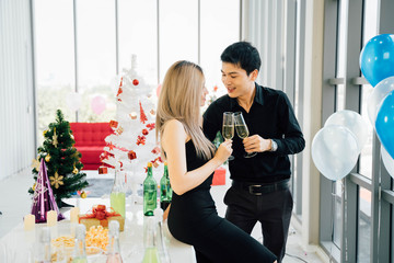 Young adult Asian couple holding a glass of wine celebrates Christmas party at luxury condo accommodation. They have snacks, gifts, and Christmas tree on table.
