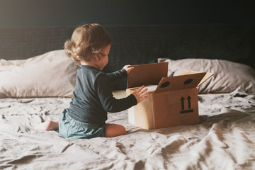 Little child playing with cardboard box on bed. Orders delivered by mail from international retail stores. Getting quality products by mail from internet stores. Quick safe shipment and money refund.