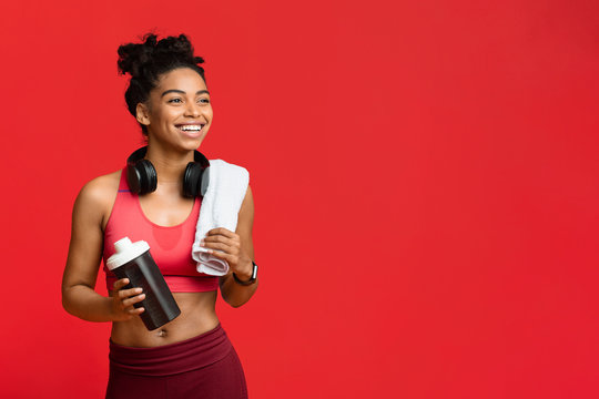 Cheerful fitness girl drinking protein during exercising