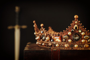 low key image of beautiful queen/king crown over antique box next to sword. fantasy medieval...