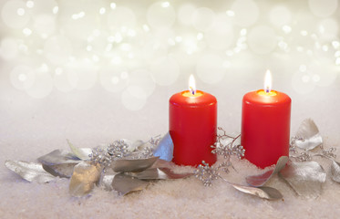 two burning candles with silvery eucalyptus leaves, copy space