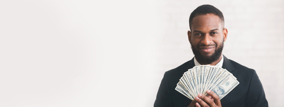 Young successful businessman holding money over white backgrpund