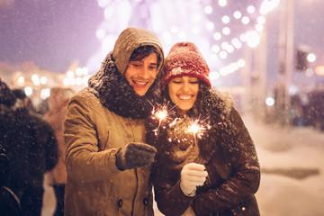 Joyful Couple Holding Bengal Lights Sparklers Celebrating New Year Outside