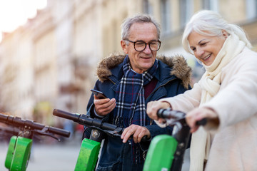 Senior couple with electric scooter and smartphone in the city