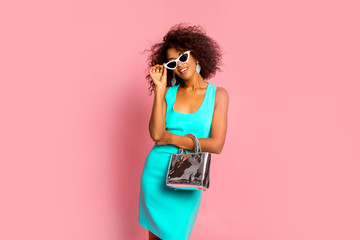 Papiers peints Salon de coiffure Beautiful african american young girl smiling and posing in stylish dress, trendy purse bag and white sunglasses at pink background in studio.Young black woman with afro hairstyle smiling.